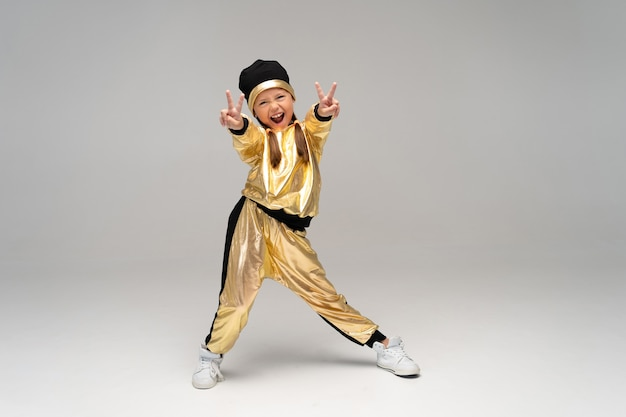 Gelukkig klein meisje in gouden pak dansen geïsoleerd op een witte ondergrond