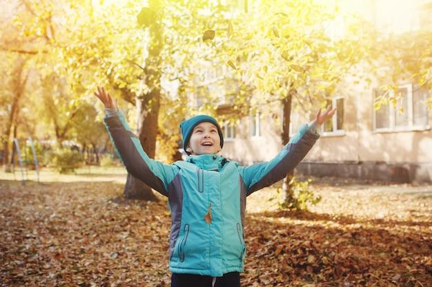 Gelukkig klein meisje in groene jas en hoed gooit herfstbladeren in het park voor een wandeling in de frisse lucht