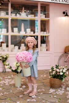 Gelukkig klein meisje in jurk en in baret met boeket pioenrozen staat in de buurt van vintage café franse stijl