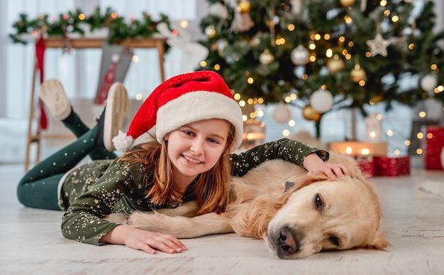 Gelukkig klein meisje in kerstmuts liggend op de vloer naast golden retriever hond in de buurt van kerstboom thuis
