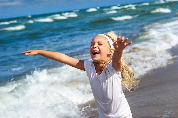 Gelukkig klein meisje in kleding op het strand van de baltische zee aan de koerse landtong in litouwen