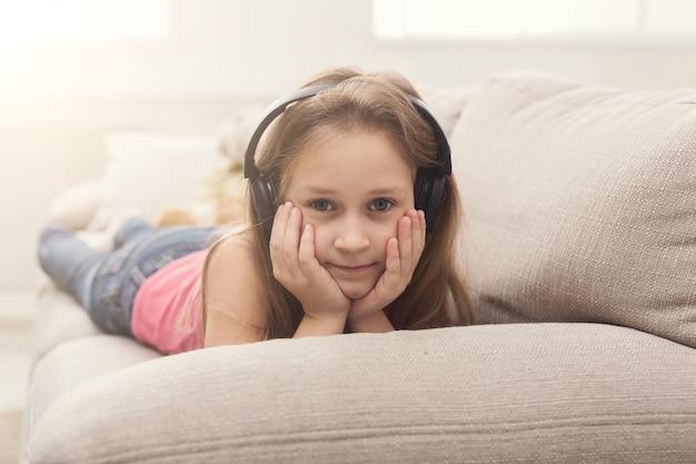 Gelukkig klein meisje in oortelefoons die naar muziek luistert terwijl ze thuis op de bank ligt, kopieer ruimte