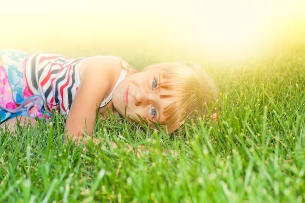 Gelukkig klein meisje in park dat in het gras ligt
