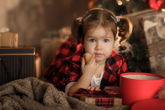 Gelukkig klein meisje in rode pyjama's en kerstmuts met kerst geschenkdoos in de woonkamer
