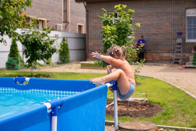 Gelukkig klein meisje in rode zwembroek springen in het buitenzwembad thuis. babymeisje die leren zwemmen. waterpret voor kinderen.