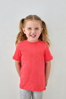 Gelukkig klein meisje in roze overhemd dat zich in studio bevindt