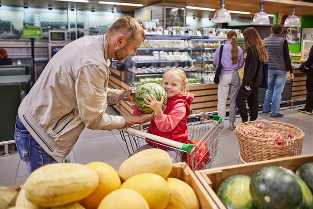 Gelukkig klein meisje in winkelwagen met vader houdt watermeloen vast