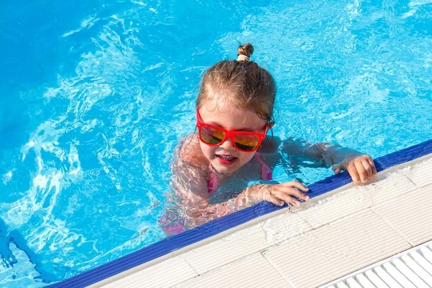 Gelukkig klein meisje in zonnebril in het zwembad in de zomer
