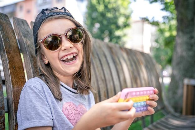 Gelukkig klein meisje in zonnebril met een smartphone in een trendy hoesje knalt het.