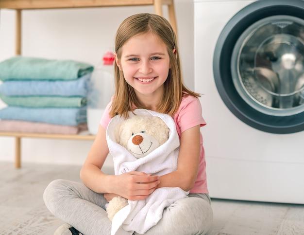 Gelukkig klein meisje knuffelen teddybeer in handdoek na het wassen op de wasmachine