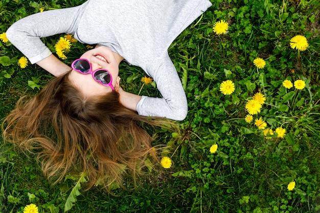 Gelukkig klein meisje lacht liggend op groen gras met paardebloemen in de zomer