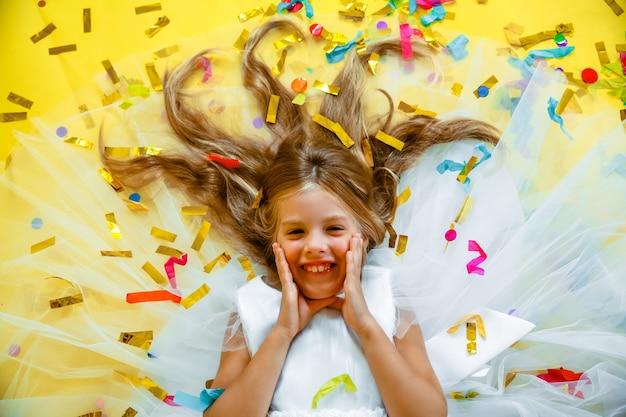 Gelukkig klein meisje met blond haar en in een witte jurk vangt confetti op een gele achtergrond, vakantieconcept