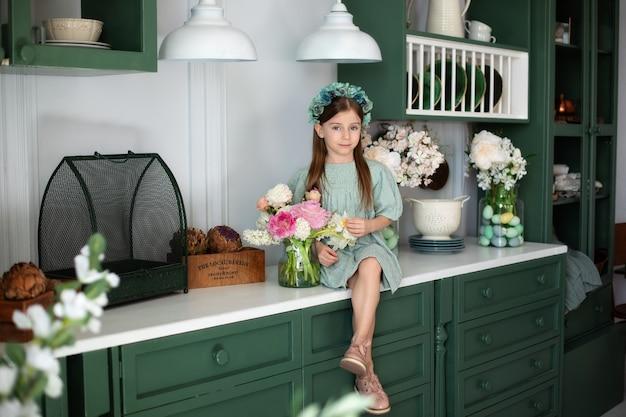 Gelukkig klein meisje met boeket bloemen in de keuken viering moederdag meisje en bloem