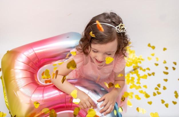 Gelukkig klein meisje met een ballon nummer vijf speelt met confetti op een witte feestelijke achtergrond. vakantie verjaardag