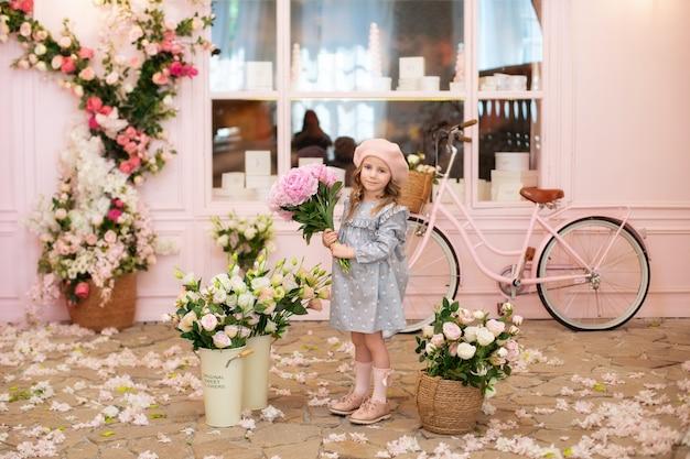 Gelukkig klein meisje met een boeket roze pioenrozen staat in de buurt van een straatcafé in franse stijl birthday mothers day celebration
