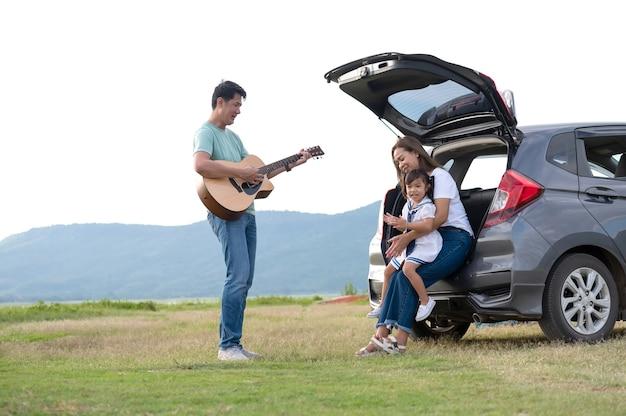 Gelukkig klein meisje met familie in de auto zitten