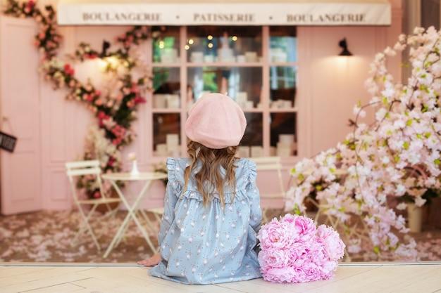 Gelukkig klein meisje met krullend haar in jurk en baret met boeket pioenrozen zittend in straat vintage café uitzicht vanaf achter franse stijl