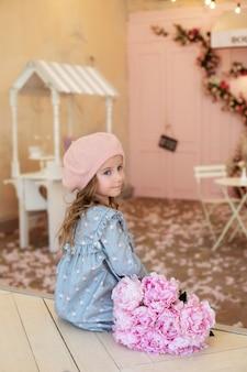 Gelukkig klein meisje met lang krullend haar in baret met een boeket pioenrozen in frans vintage café