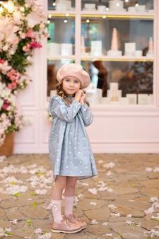 Gelukkig klein meisje met lang krullend haar in een blauwe jurk en baret staat in frans vintage café