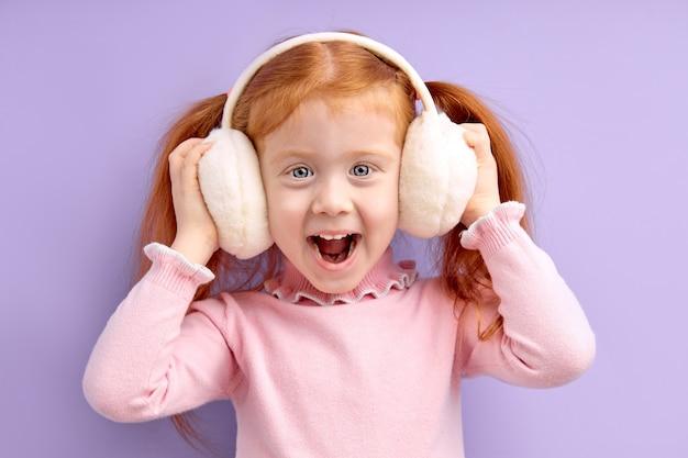 Gelukkig klein meisje met rood haar staan draadloze koptelefoon dragen genieten van het luisteren naar muziek