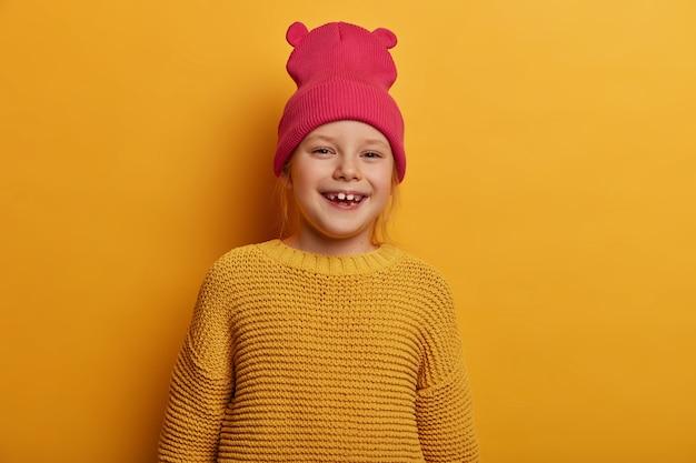 Gelukkig klein meisje met tevreden uitdrukking kijkt direct, glimlacht positief, drukt oprechte emoties uit, voelt zich vrolijk, draagt roze hoed met oren en gebreide gele trui, vormt binnen