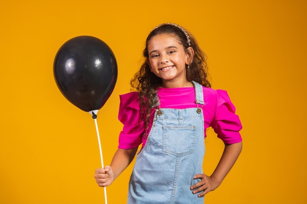 Gelukkig klein meisje met zwarte ballon met black friday-concept. verkoop jubileum