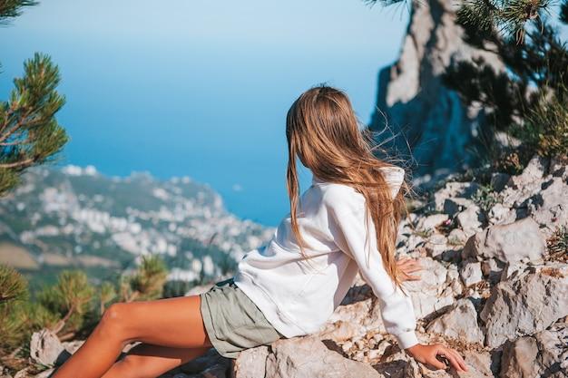 Gelukkig klein meisje op de rand van de klif genieten van het uitzicht op de rots van de bergtop