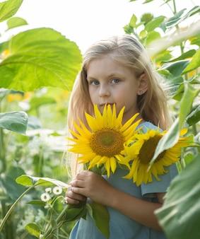 Gelukkig klein meisje op het gebied van zonnebloemen in de zomer.