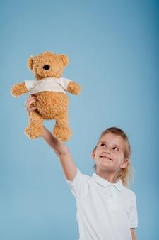Gelukkig klein meisje pak het speelgoed van de teddybeer op geïsoleerd op een blauwe achtergrond studio-opname kijk naar de camera