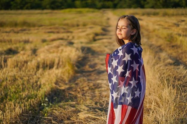 Gelukkig klein meisje patriot uitgevoerd in het veld met amerikaanse vlag.