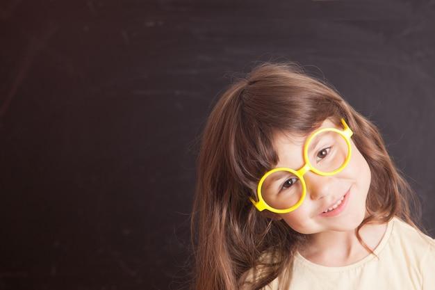 Gelukkig klein meisje schoolmeisje van het bord