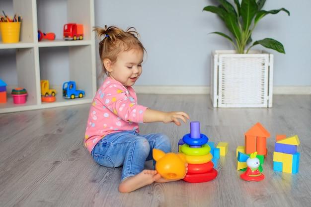 Gelukkig klein meisje spelen met speelgoed thuis, in de kleuterschool of kinderkamer. ontwikkeling van het kind.