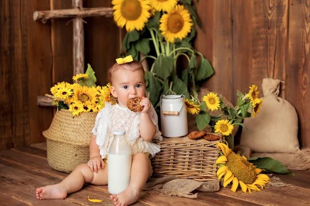 Gelukkig klein meisje spelen onder bloeiende zonnebloemen in de buurt van de mand. kind dat koekjes met melk eet