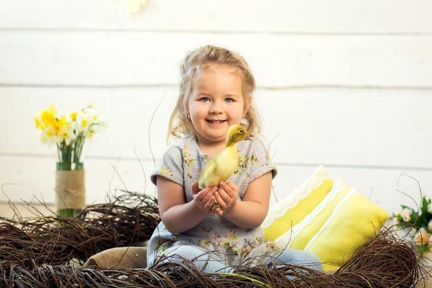 Gelukkig klein meisje wordt gespeeld met schattige donzige paaseendjes.