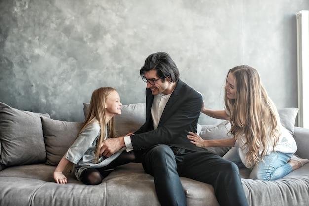 Gelukkig klein meisjesspel met haar moeder en vader op de bank
