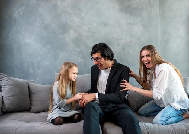 Gelukkig klein meisjesspel met haar moeder en vader