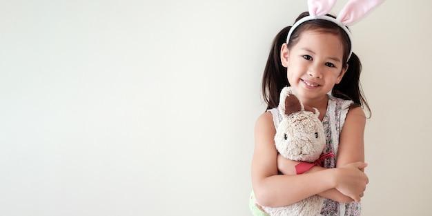 Gelukkig klein multicultureel asainmeisje met konijntjeskonijn, pasen-jong geitje