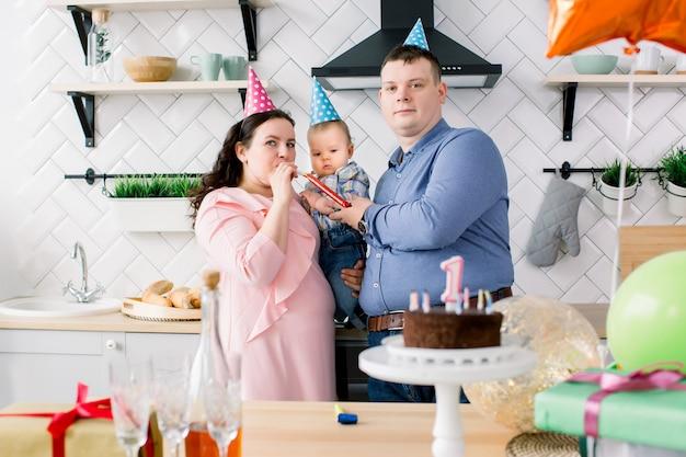 Gelukkig kleine babyjongen, vader en moeder met trompetten en ballonnen op verjaardagsfeestje. jong gezin viert verjaardag met een taart