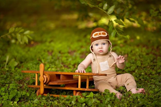 Gelukkig kleine babyjongen van 8-12 maanden oud vliegt op een vliegtuig in de natuur. baby piloot
