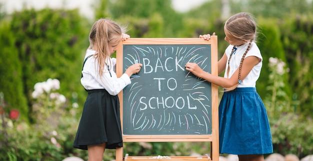 Gelukkig kleine schoolmeisjes met een schoolbord buiten
