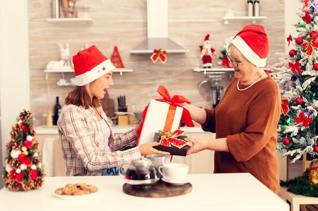 Gelukkig kleinkind dat kerst viert en cadeautjes uitwisselt met oma