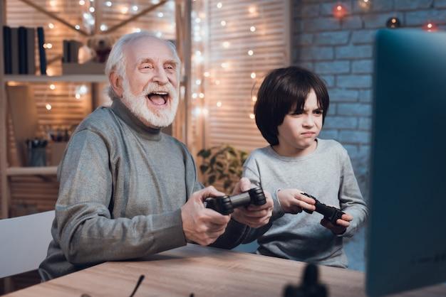 Gelukkig kleinzoon spelen van videogame met grootvader