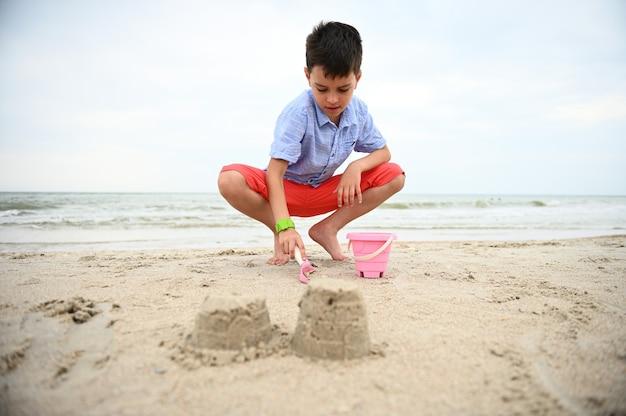 Gelukkig knap en schattig jongenskind peuter speelgoed emmer vullen met zand voor het bouwen van sandcastl