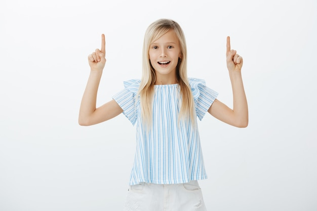 Gelukkig knap jong meisje met blond haar, vrolijk gevoel terwijl ze wijsvingers opheft en naar boven wijst