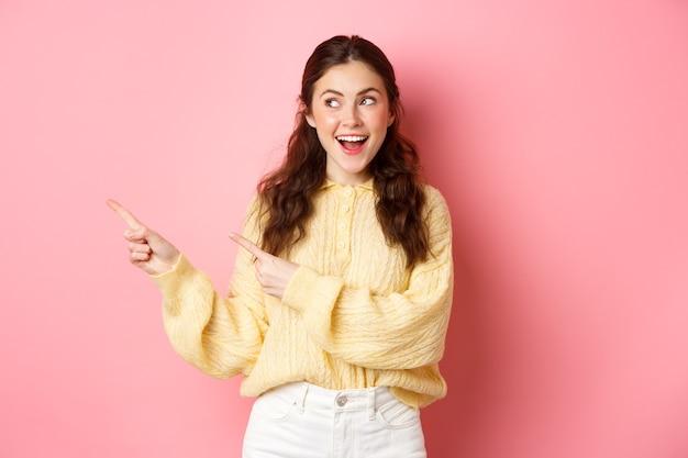 Gelukkig knap meisje demonstreren informatie, wijzende vingers naar links en starend naar promotietekst met tevreden glimlach, staande tegen roze muur.