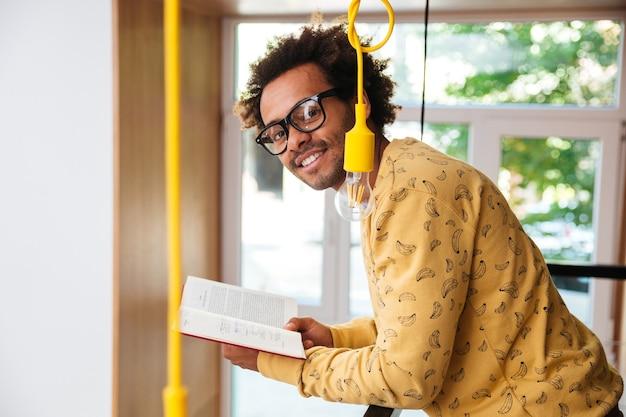 Gelukkig knappe afrikaanse jongeman in glazen lezen van een boek thuis
