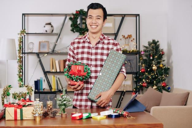 Gelukkig knappe jonge aziatische man aan tafel met ingepakte cadeautjes en kerstkrans in handen