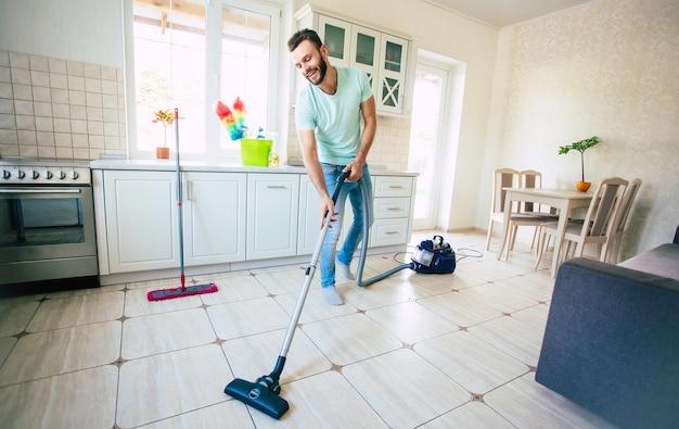 Gelukkig knappe jonge baard man is het schoonmaken van de vloer in de binnenlandse keuken en veel plezier.