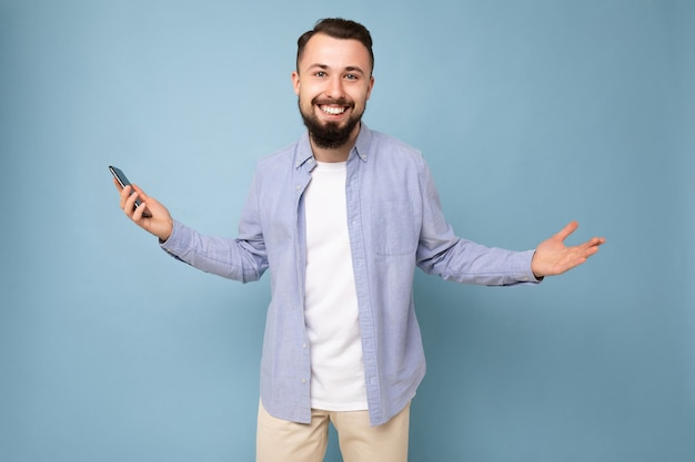 Gelukkig knappe jonge brunette ongeschoren man met baard met stijlvolle witte t-shirt en blauw shirt