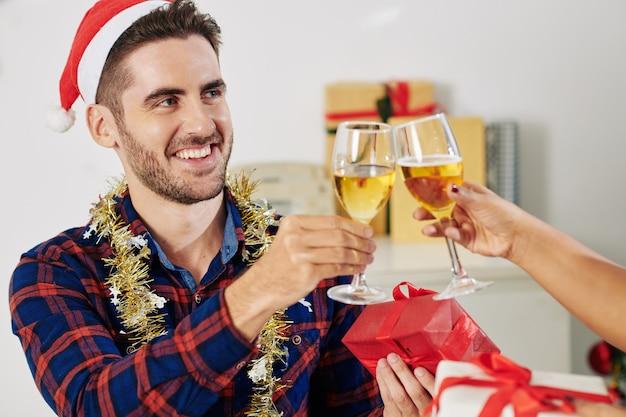 Gelukkig knappe jonge kantoormedewerker in kerstmuts met klatergoud om zijn nek roosteren met collega bij het vieren van kerstmis